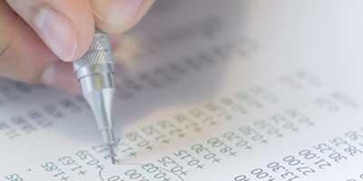 Foto di una mano in primo piano che tiene in pugno una matita portamine appoggiata su un foglio di calcolo con cifre stampate